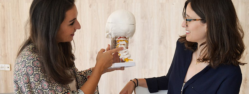 two women smiling, pointing to a skull and talking about neural diseases and the MeedTech industry