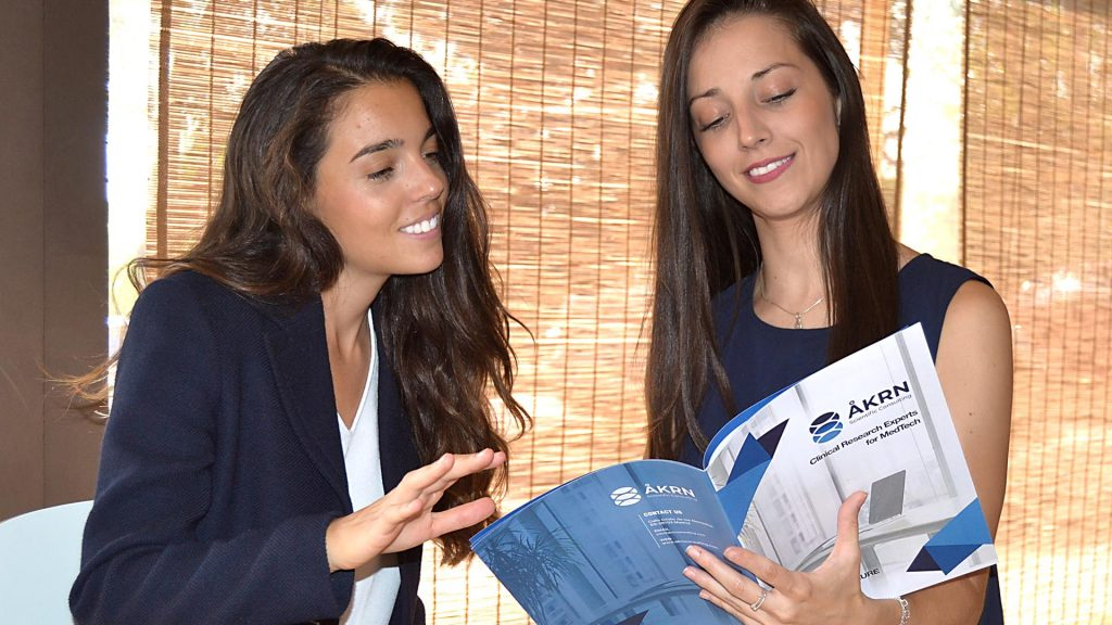 Two women looking at the AKRN service brochure. Clinical Data Management services as CRFs, IB