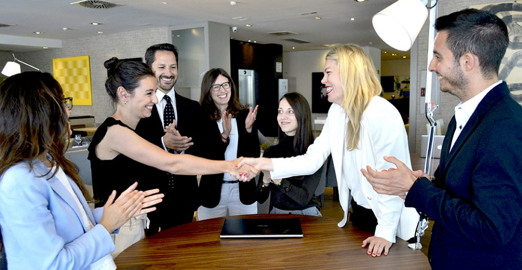 two women shaking hands and the rest of the AKRN team happy for beign part of the MedTech Industry